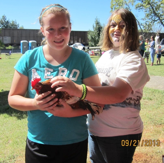 Marica Hunsperger, 12, of Koshkonong holds her prize chicken, accompanied by a friend.