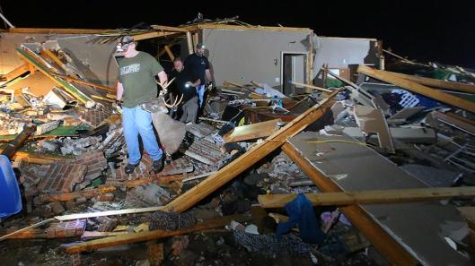 Residents salvage items from their home in a subdivision where fatalities occurred in Vilonia, Ark., after a tornado struck there April 27. (Weather Channel photo by Stephen B. Thornton)