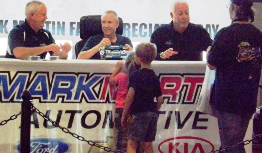 Mark autographs a car for two young fans. (Staff photo by Mariann Hyslop)