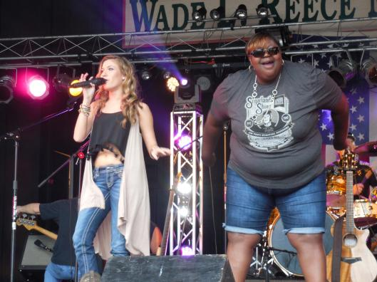 """Big Juicy, co-star of truTV's """"Lizard Lick Towing,"""" joins singer/songwriter Kaitlyn Baker on stage.  (Photo courtesy of Fred Anderson)"""