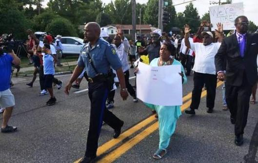 Highway Patrol Capt. Ron Johnson joins protesters in their march in Ferguson, Mo., Thursday night.
