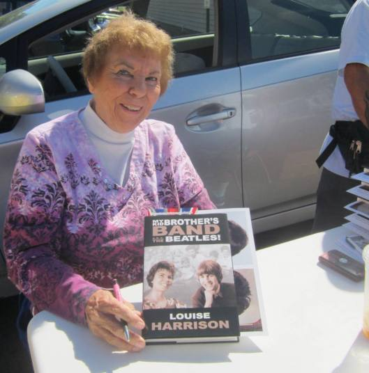 "Louise Harrison shows off her book ""My Kid Brother's Band: The Beatles!"" at the Beatlemania festival in Alton. (Hill 'n Holler staff photo)"