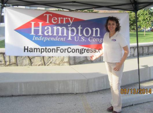 Terry Hampton, Independent candidate for Congress from the 8th District, shows off her new banner. (staff photo)
