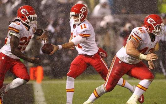 Chiefs quarterback Alex Smith hands the ball to Jamaal Charles during heavy rain in Oakland Thursday night. (Kansas City Chiefs photo)