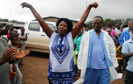 An Ebola survivor, accompanied by a medical director, is being welcomed by her community in the Firestone District of Liberia. (CDC photo)