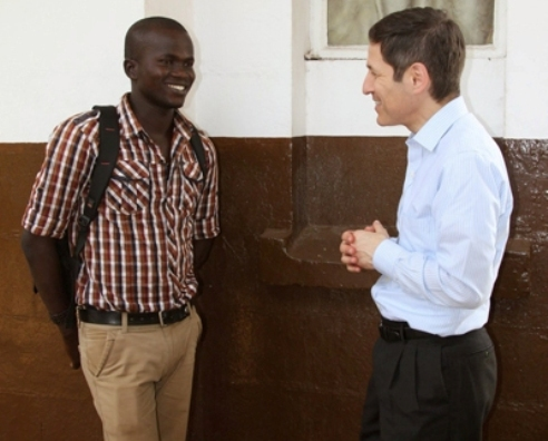 Tom Frieden, right,  speaks with Yusif Koroma, an Ebola survivor who is now taking in orphans at a nearby social services center. (CDC photo)