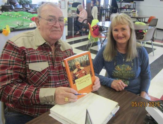 """Author Bill Combs signs a book for Thayer resident Beverly Martin. His book """"Oregon County Growing Up"""" is chock full of stories about what it was like to grow up in Oregon County back in the '40's and '50's. (Hill 'n Holler staff photo)"""