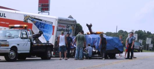 (Above and below) Workers put their backs into it in an effort to get this moving truck and trailer moving again. (Hill 'n Holler staff photos)