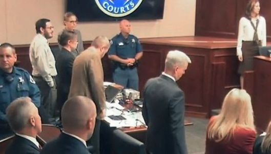James Holmes, at left in white shirt, and his attorneys listen to the reading of verdicts Thursday afternoon.