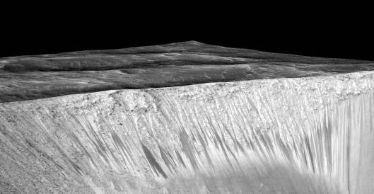 Dark narrow streaks called recurring slope lineae emanating out of the walls of Garni crater on Mars. The dark streaks here are up to few hundred meters in length. They are hypothesized to be formed by flow of briny liquid water on Mars. The image is produced by draping an orthorectified (RED) image (ESP_031059_1685) on a Digital Terrain Model (DTM) of the same site produced by High Resolution Imaging Science Experiment (University of Arizona). Vertical exaggeration is 1.5.  (Credits: NASA/JPL/University of Arizona)