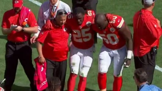 Injured Jamaal Charles is helped off the field.