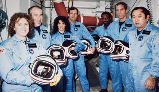 In this photo from Jan. 9, 1986, the Challenger crew takes a break during countdown training at NASA's Kennedy Space Center. Left to right are Teacher-in-Space payload specialist Sharon Christa McAuliffe; payload specialist Gregory Jarvis; and astronauts Judith A. Resnik, mission specialist; Francis R. (Dick) Scobee, mission commander; Ronald E. McNair, mission specialist; Mike J. Smith, pilot; and Ellison S. Onizuka, mission specialist.  (NASA photo)