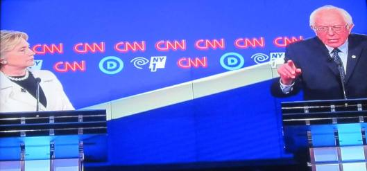 Hillary Clinton and Bernie Sanders on stage.  (Hill 'n Holler photo of CNN debate broadcast on line)