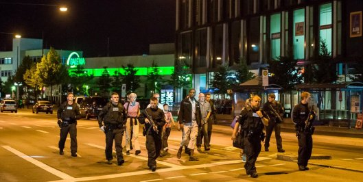 Police officers escort people from inside the shopping center as they respond to a shooting at the Olympia Einkaufzentrum (OEZ) at July 22, 2016 in Munich, Germany. (Getty Image by Joerg Koch from Huffington Post)