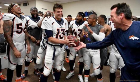 Coach Gary Kubiak hands quarterback Trevor Siemian the game ball after the game Sunday. (Denver Broncos photo by Eric Bakke